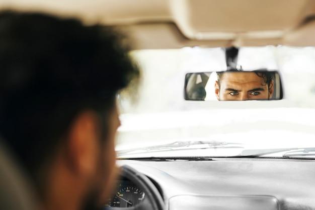 Achtermening van de mens die autospiegel controleren