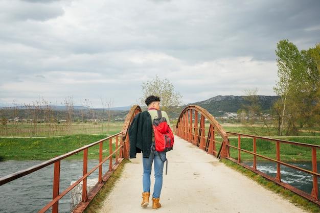 Achtermening van de mens die op brug over rivier lopen
