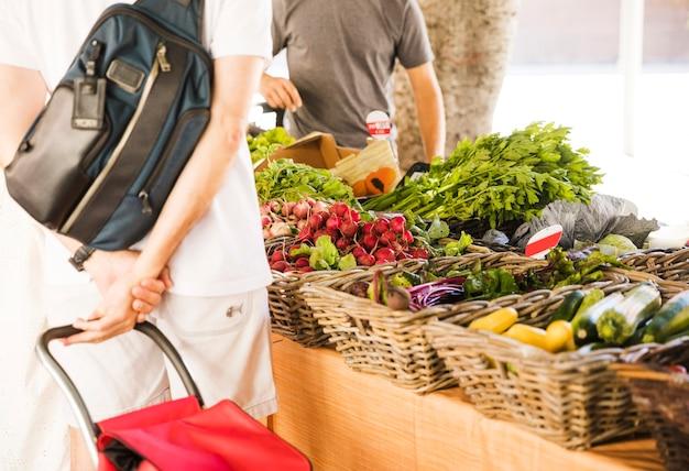 Achtermening van de mens die organische groente bij markt kopen