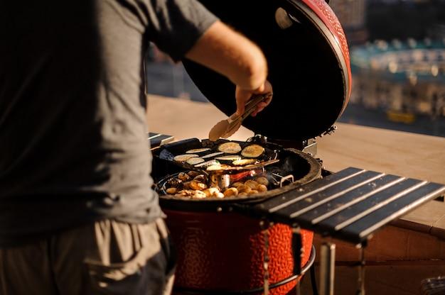 Achtermening van de mens die verse groenten op de barbecuegrill koken op zonnige dag