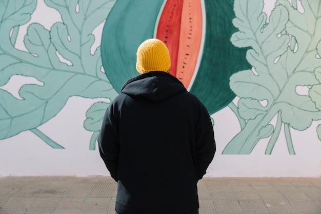 Achtermening van de mens die zich voor graffitimuur bevindt