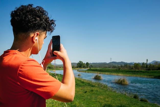 Achtermening van de mens met oortelefoon die beeld op smartphone nemen