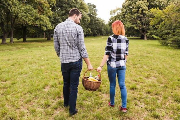 Achtermening van de picknickmand die van de paarholding in park lopen