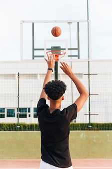 Achtermening van de sportieve mens die bal in hoepel werpen
