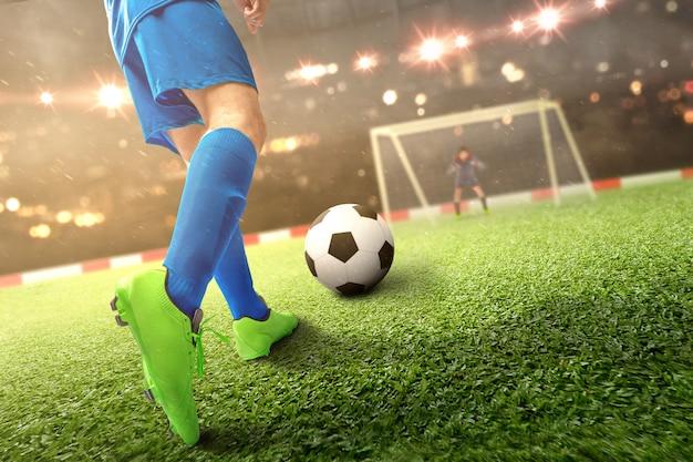 Achtermening van de voetballermens die de bal op het voetbalgebied schoppen