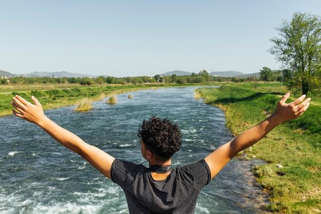 Achtermening van de zorgeloze mens die zich dichtbij rivier bevindt