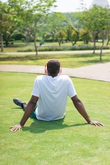 Achtermening van de zwarte mens die op gras met draadloze hoofdtelefoons rusten.