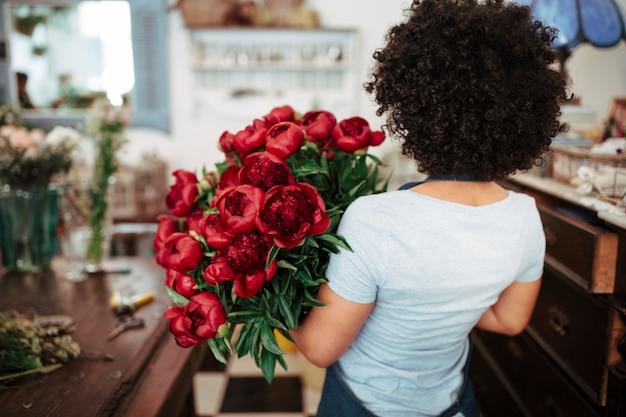 Achtermening van een afrikaanse vrouwelijke bloemist met bos van rode bloemen