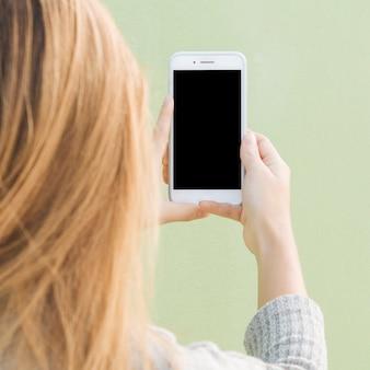 Achtermening van een blonde jonge vrouw die mobiele telefoon houden tegen munt groene achtergrond