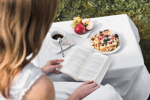 Achtermening van een boek van de vrouwenlezing met ochtend gezond ontbijt op lijst bij openlucht
