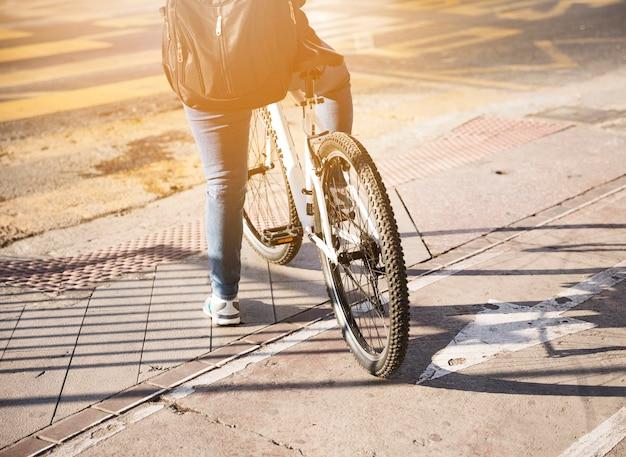 Achtermening van een fietser met rugzak die op weg wachten
