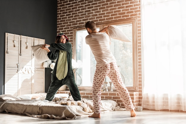 Achtermening van een jong paar die met hoofdkussen in de slaapkamer vechten