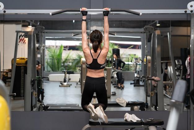 Achtermening van een jonge aantrekkelijke vrouw die omhoog op een kin omhoog baroefening in een gymnastiek uittrekken.