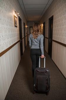 Achtermening van een jonge vrouw die haar koffer in de hotelgang trekt