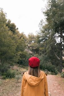 Achtermening van een jonge vrouw in rode gebreide hoed die zich op de manier aan bos bevinden