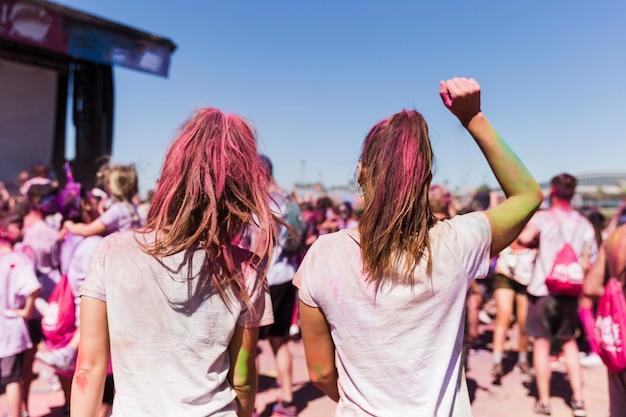 Achtermening van een jonge vrouw twee die in holifestival dansen
