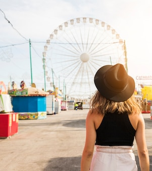 Achtermening van een jonge vrouw voor reuzemuur bij pretpark