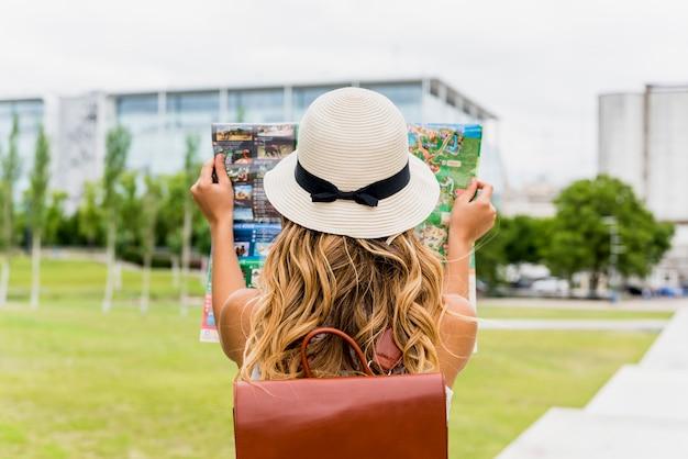 Achtermening van een jonge vrouwelijke toerist die de kaart van de hoedenlezing in het park dragen