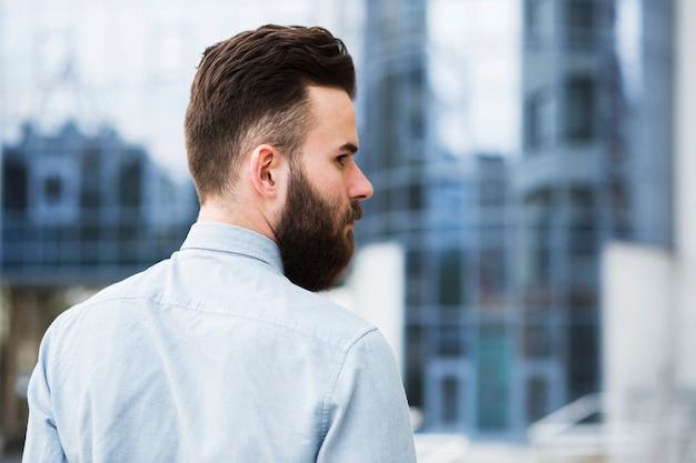 Achtermening van een jonge zakenman die over zijn schouder kijkt