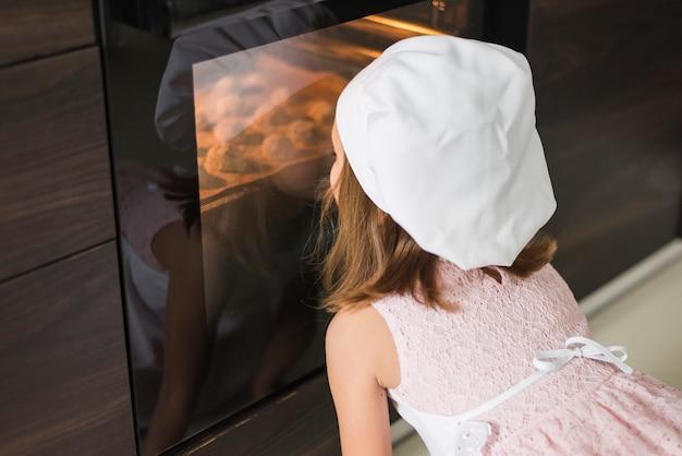 Achtermening van een klein meisje die in chef-kokhoed koekjesdienblad bekijken in oven