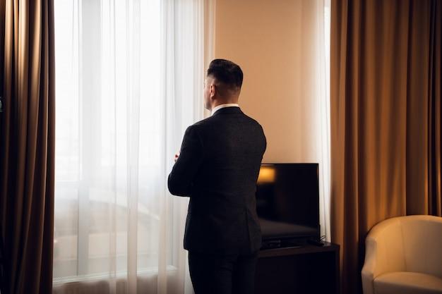 Achtermening van een knappe elegante jonge zakenman die zijn manchetten in een hotelsuite aanpassen.