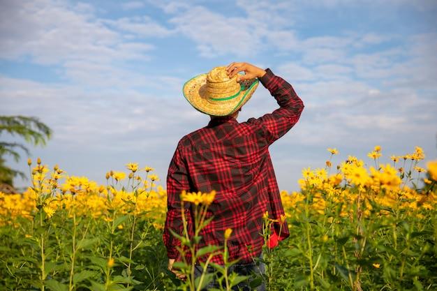 Achtermening van een landbouwarbeider die een rood overhemd in een gele bloemtuin draagt.