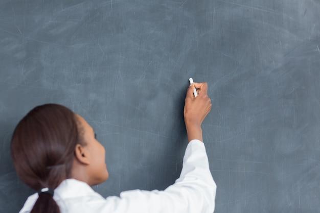 Achtermening van een leraar die op een bord schrijft
