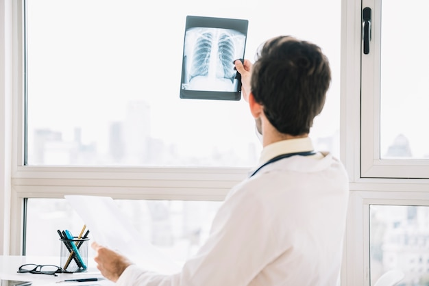 Achtermening van een mannelijke arts die borströntgenstraal onderzoekt