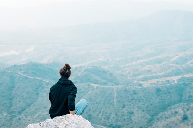 Achtermening van een mannelijke wandelaarzitting bovenop rots die bergmening overzien