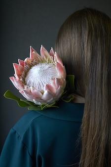 Achtermening van een meisje die met donker haar een roze proteabloem op een donkere achtergrond, selectieve nadruk houden