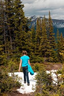 Achtermening van een meisje die op sneeuw behandelde sleep, kale heuvels, jasper national park, alberta, canada lopen
