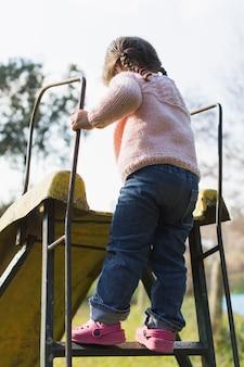 Achtermening van een meisje die zich op dialadder bevinden in het park