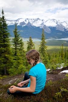 Achtermening van een meisjeszitting met bergketen op de achtergrond, de kale sleep van heuvels, het nationale park van de jaspis, alberta, canada