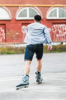 Achtermening van een mens die buiten rolt schaatsen