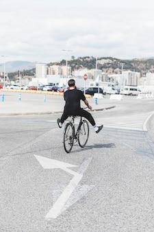 Achtermening van een mens die de fiets berijden op weg