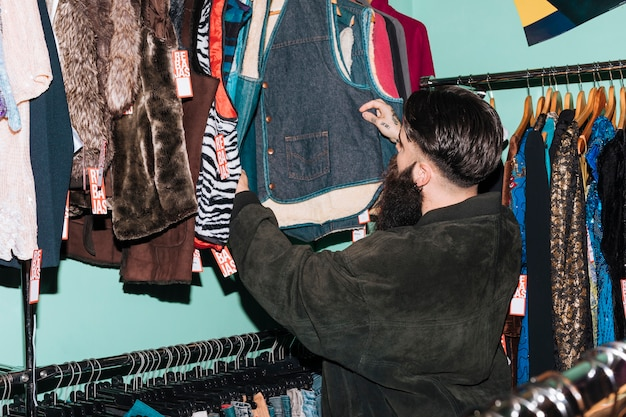 Achtermening van een mens die kleren kiezen die op het spoor in de kledingswinkel hangen