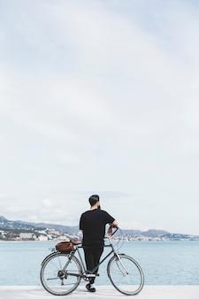 Achtermening van een mens die met fiets baai bekijkt