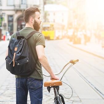 Achtermening van een mens met zijn fiets in stad