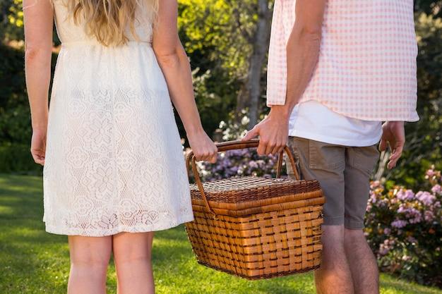Achtermening van een paar die een picknickmand in de tuin samenhouden