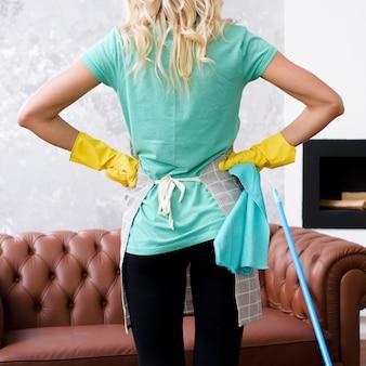Achtermening van een reinigingsmachine die gele rubberhandschoenen draagt die zich met haar handen op heupen bevinden