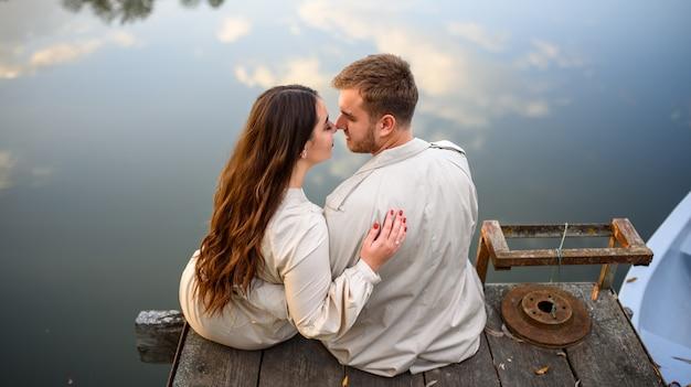 Achtermening van een romantische jonge paarzitting op de pijler die van mooi meer genieten.