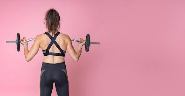 Achtermening van een vrouw die gewichtheffen met barbell doet