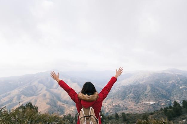 Achtermening van een vrouw die met rugzak haar wapens opheffen die bij berglandschap overzien