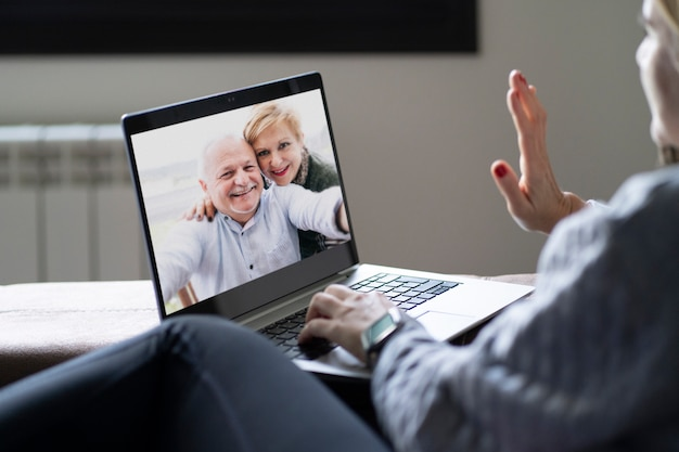 Achtermening van een vrouw die op een familievideogesprek met haar ouders van huis spreken