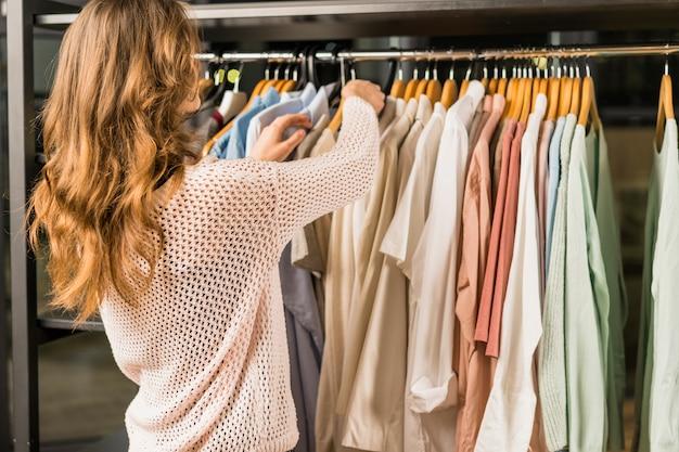 Achtermening van een vrouwelijke klant die kledingstukken selecteren bij de opslag