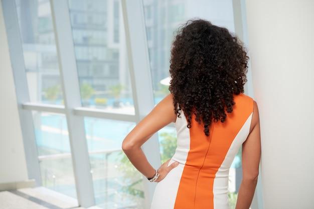 Achtermening van elegante krullende vrouw die het venster bekijken