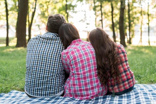 Achtermening van familiezitting in park met het leunen van hun hoofden op elke anderen schouder