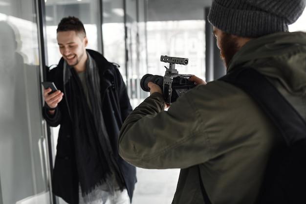 Achtermening van fotograaf die knap mannelijk model buiten schieten.