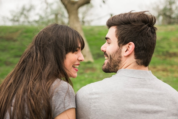 Achtermening van glimlachend jong paar die elkaar bekijken