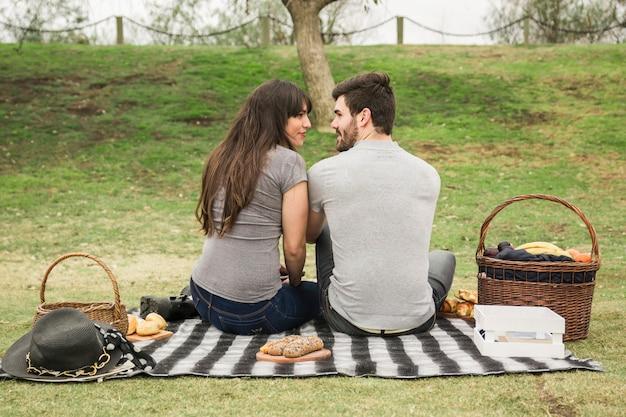 Achtermening van glimlachend jong paar die elkaar op picknick bekijken
